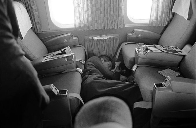 An image of Kennedy sleeping on the floor of a plane